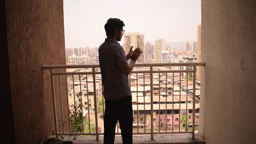 Young man clap hands in balcony to thank, applaud doctors, nurses, health workers, police on Janata curfew day during coronavirus outbreak in Mumbai, Maharashtra, India, 22 March 2020 Royalty-Free Stock Footage #1050945445