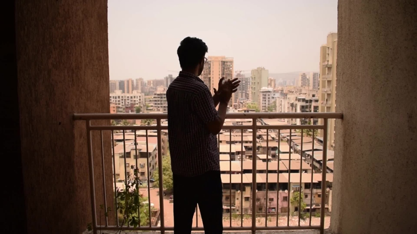 Young man clap hands in balcony to thank, applaud doctors, nurses, health workers, police on Janata curfew day during coronavirus outbreak in Mumbai, Maharashtra, India, 22 March 2020 Royalty-Free Stock Footage #1050945454