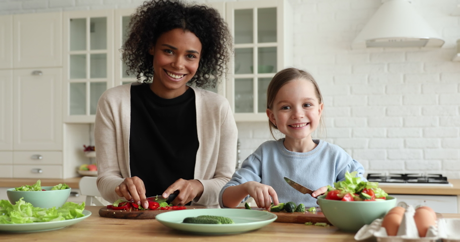Happy mixed race vegan family young foster african mom and cute small caucasian adopted child daughter enjoy cooking together, preparing healthy organic vegetable salad, looking at camera. Portrait.