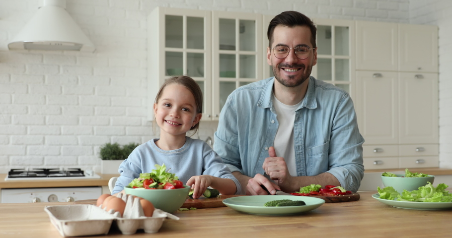 Happy cute small kid daughter cooking with father looking at camera stand at kitchen table. Young dad teaching child learning preparing healthy food cutting vegetable salad. Vegan family making meal.
