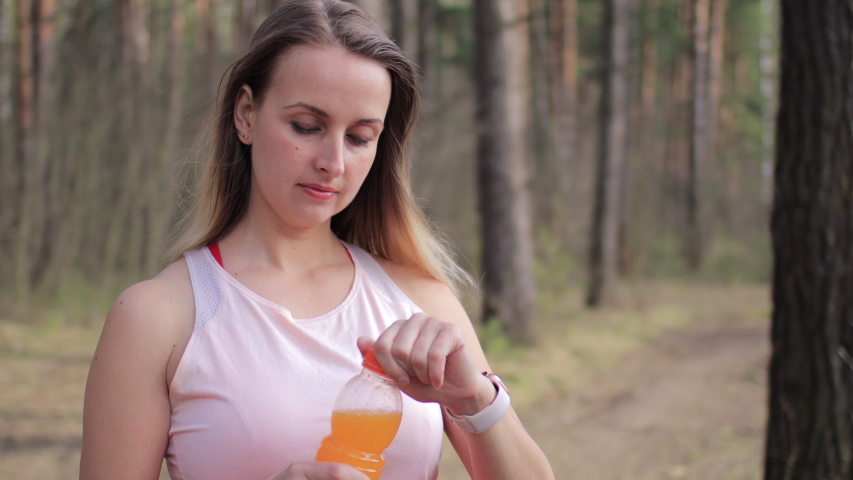 Woman drink orange juice from bottle in the park after walking at spring day