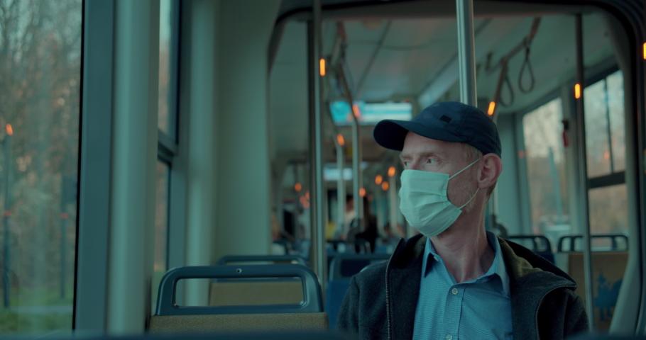 Man in face mask traveling on tram   Shutterstock HD Video #1050974092