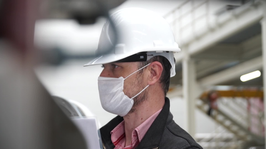 worker/engineer wearing disposal face mask for protect dust smoke and corona virus while working in workplace or factory. Royalty-Free Stock Footage #1050977662