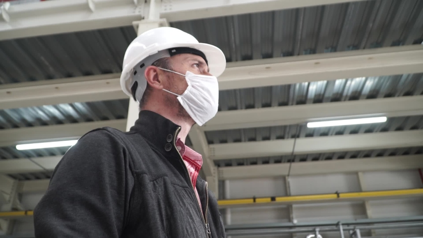 Worker/engineer wearing disposal face mask for protect dust smoke and corona virus while working in workplace or factory.Camera turning around a worker.