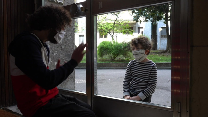 Europe, Italy , Milan dad nurse and 5 year old male with mask meet during covid19 Coronavirus quarantine and speak through a glass - isolation and separation to defeat the virus and global epidemic  Royalty-Free Stock Footage #1050993889