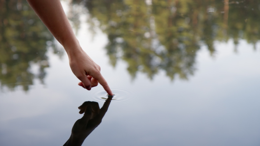 Gentle female hand touch serene and calm water surface of quiet lake. Peaceful and mindful connection with nature. Finger touch clean water in forest lake. Pure yoga or meditation inspiration