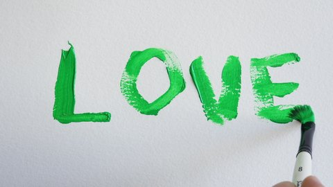 Green Paint Brushstrokes Write Love, Chroma Key Background. Hand with a brush writes the word love with chroma key color paint. Time lapse