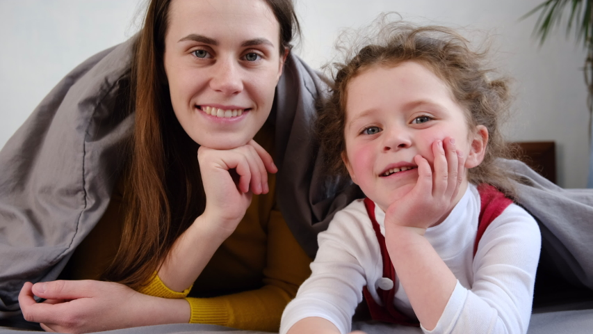 Happy mom and little kid child daughter lying on bed covered with blanket talking video calling on chatting laughing enjoy online conversation looking at webcam, family vloggers recording video  Royalty-Free Stock Footage #1051002175