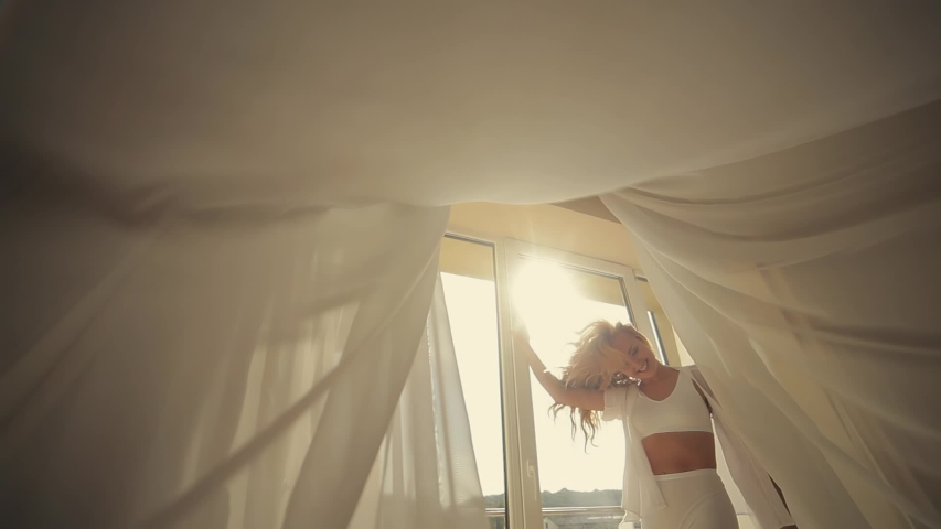 Pastel shades. attractive having fun, rejoicing, cheerful lady by the window against the background light in the morning lounge room with bed and white, girl in lingerie, blonde. Pretty fresh fitness | Shutterstock HD Video #1051010182