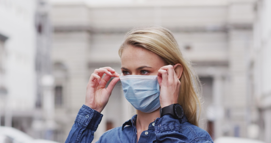 Caucasian woman putting on a face mask against coronavirus, covid 19 out and about in the city streets during the day. | Shutterstock HD Video #1051010335