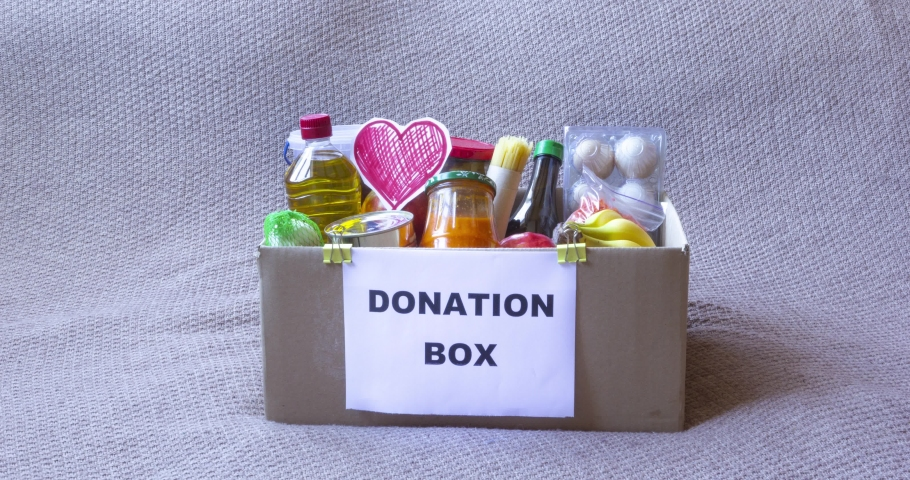 Food donation box stop motion animation. Products get into the box, a hand in a protective glove puts the heart inside. Coronavirus epidemic, 2019-nCoV Covid-19 pandemic. Quarantine