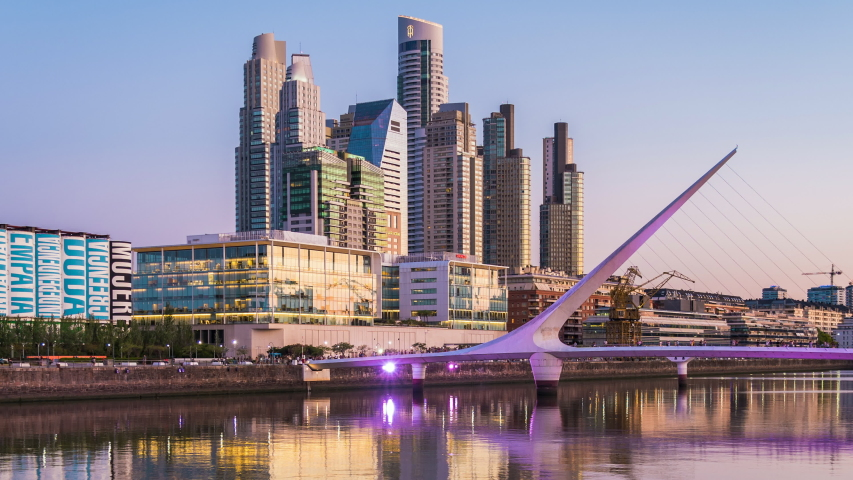 Buenos Aires, Argentina - February 02, 2020: Day to night timelapse view of Puerto Madero including architectural landmark Puente de la Mujer in Buenos Aires, Argentina, zoom out.