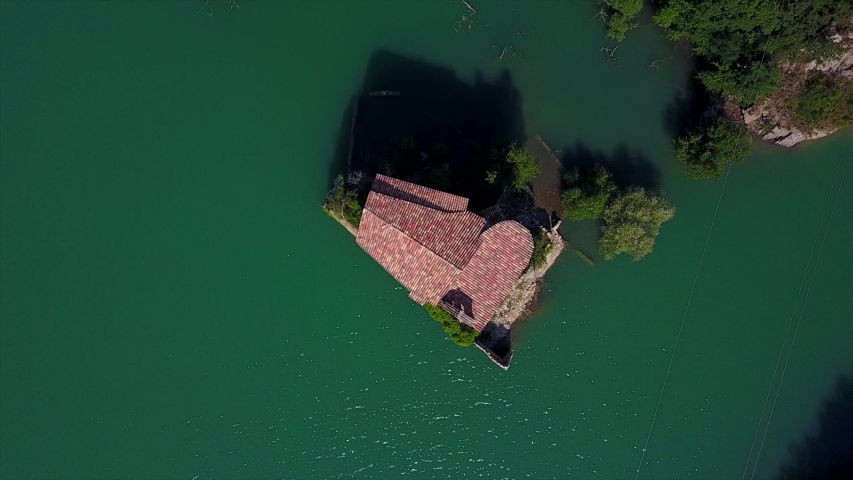 Top down aerial view of church roof in the middle of a lake. Flooded Ruins of an ancient monastery  | Shutterstock HD Video #1051022233