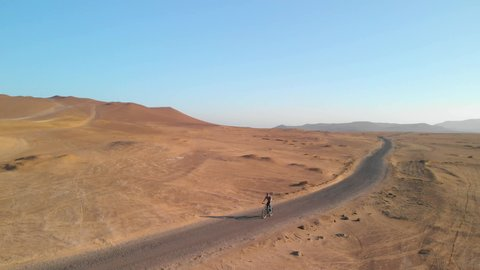 Aerial view/ tracking drone shot of a young man riding a bike on a road through the beautiful dry desert landscape of Paracas National Reserve in Peru, South America