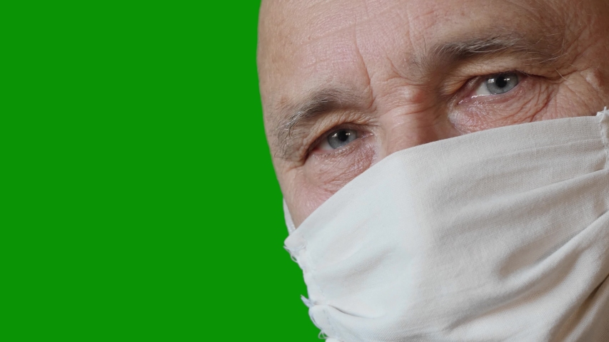 Scared elderly man in a handmade improvised protective mask on copy space green screen chroma key background. Health and safety concept for older people during the COVID-19 coronavirus pandemic   Shutterstock HD Video #1051047853