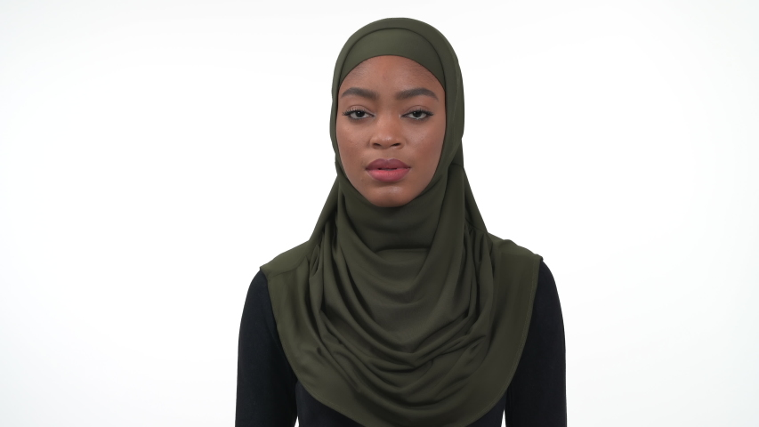 Portrait of a young african woman in green hijab and black roll-neck polo raises her hand and sneezing into elbow. Right way to cover your cough. Isolated on the white background. Royalty-Free Stock Footage #1051055581