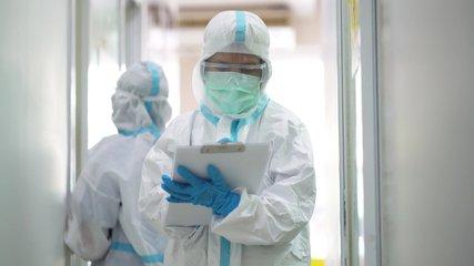 Asian doctor holding checking coronavirus or covid-19 infected patient name list sheet in quarantine area in hospital. Corona virus, Covid 19 virus outbreak, medical mask or virus outbreak concept