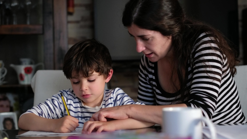 Mother and son doing homework at home living room, correcting with rubber