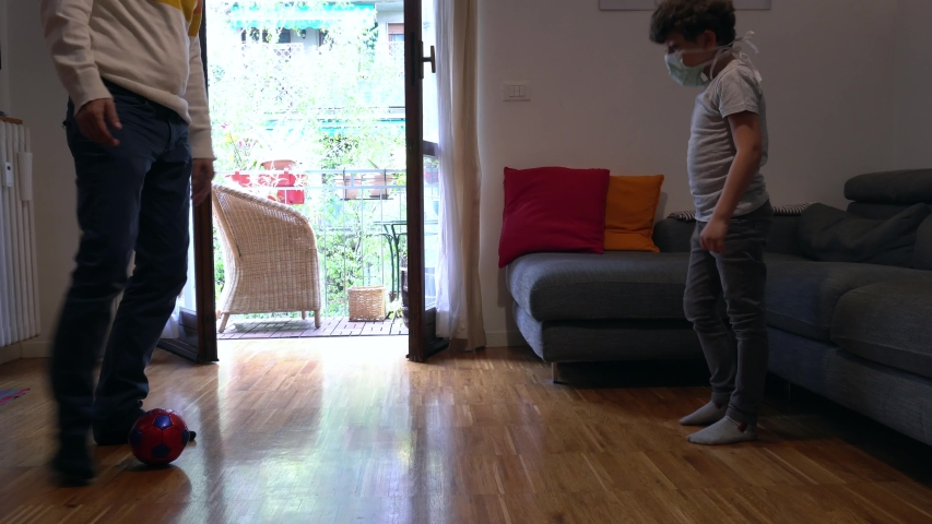 Europe, Italy , Milan - Father and children boy  five years with mask at home during quarantine due n-cov19 Coronavirus outbreak - life stile in apartment, playing soccer football in house living room Royalty-Free Stock Footage #1051059352