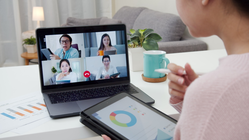 Back view of business woman talking about sale report in video conference.Asian team using laptop and tablet online meeting in video call.Working from home, Working remotely and Self isolation at home Royalty-Free Stock Footage #1051063630