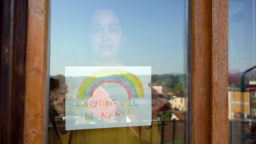 Caucasian south american girl with dark hair yellow shirt holding a sign saying everything will be alright behind her window during covid-19 lockdown