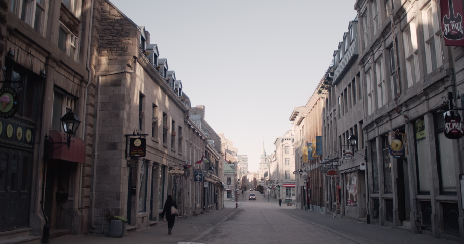 MONTREAL, QUEBEC - MARCH 27, 2020: A few random people walk the streets in historic Montreal city empty and barren during quarantine due to coronavirus pandemic