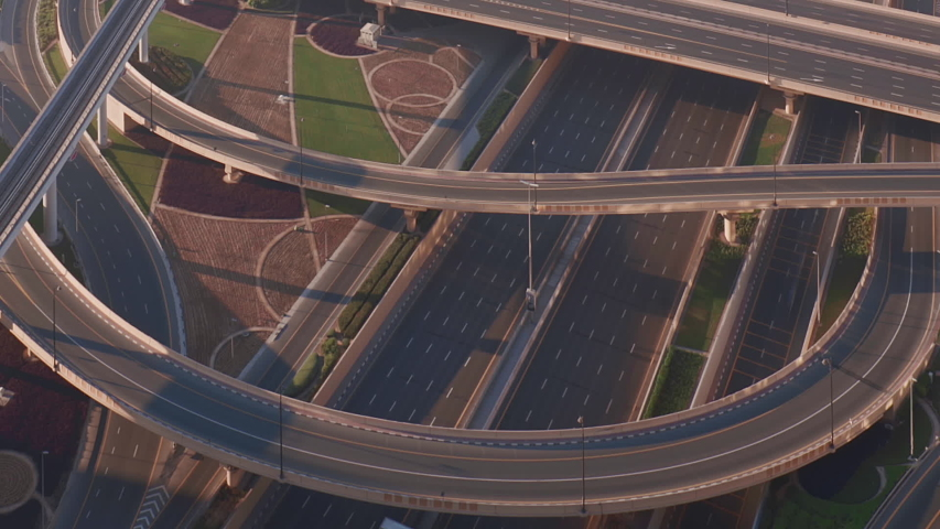 Aerial view of empty highway interchange in Dubai downtown after epidemic lockdown. Cityscapes with appearing traffic on a bridge and streets. Roads and lanes crossroads without cars, Dubai, United Royalty-Free Stock Footage #1051077181