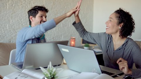 Focused Young freelancer couple sitting at desk working hard and celebrating with high five new job. Indoors at home living room. Freelance, home office, remote work, online concept.