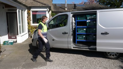 4K: Grocery delivery driver from Supermarket lifts a crate of food out of the van - He is wearing a face mask and gloves. Stock Video Clip Footage
