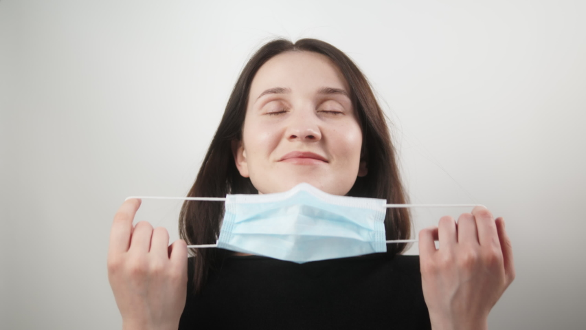 Happy positive girl, young beautiful woman takes off protective medical mask from face, smiling. Happy end quarantine and home isolation. Victory over coronavirus. Pandemic Covid-19. | Shutterstock HD Video #1051088587