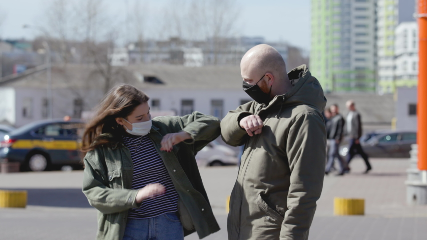 Friends use elbow bump as an alternative greeting to help prevent spread of disease. Young people in medical masks communicate at distance during epidemic. Royalty-Free Stock Footage #1051091548