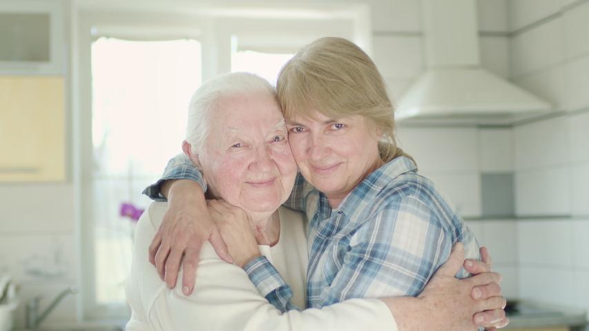 Portrait Of Two Women. Daughter Hugs Her Old Mom. Women In The Kitchen. | Shutterstock HD Video #1051120750