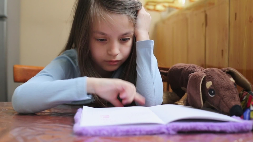 Child girl doing homework writing and reading at home   Shutterstock HD Video #1051123537