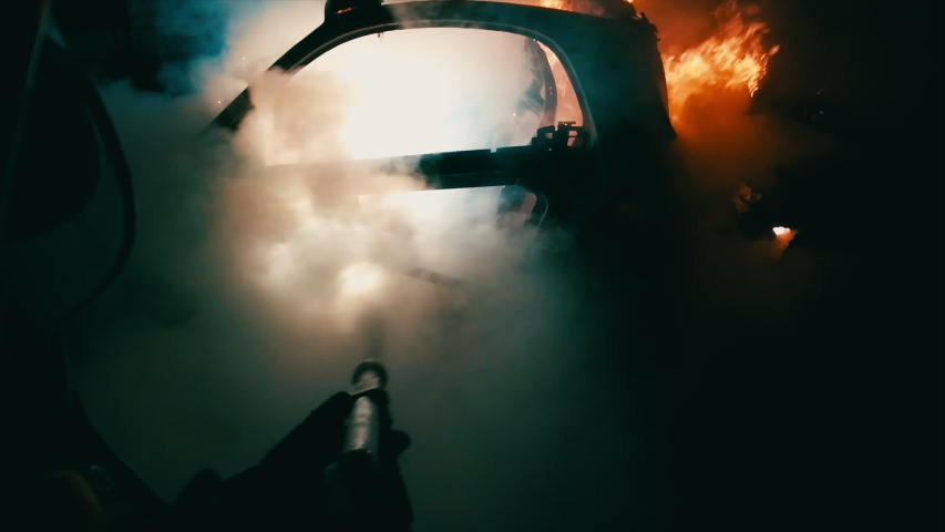 Firefighter in action. fire and rescue. flames in the night. adrenaline scene in first person. point of view of the fireman. a team of firefighters extinguishes a fire that is destroying a car | Shutterstock HD Video #1051125658