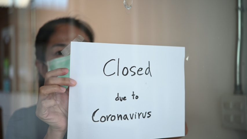 Asian business owner woman wearing face mask or small shop manager attaching business closed sign at shop entrance due to financial crisis from coronavirus covid-19 epidemic outbreak over the world.
