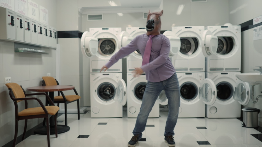 Joyful Man in mask horse Dancing Cheerful In Laundry Room. Man Dancing Viral Dance And Have Fun In Laundry Room. Happy Guy Enjoying Dance, Having Fun Together, Party Halloween. Slow Motion. Halloween | Shutterstock HD Video #1051136233