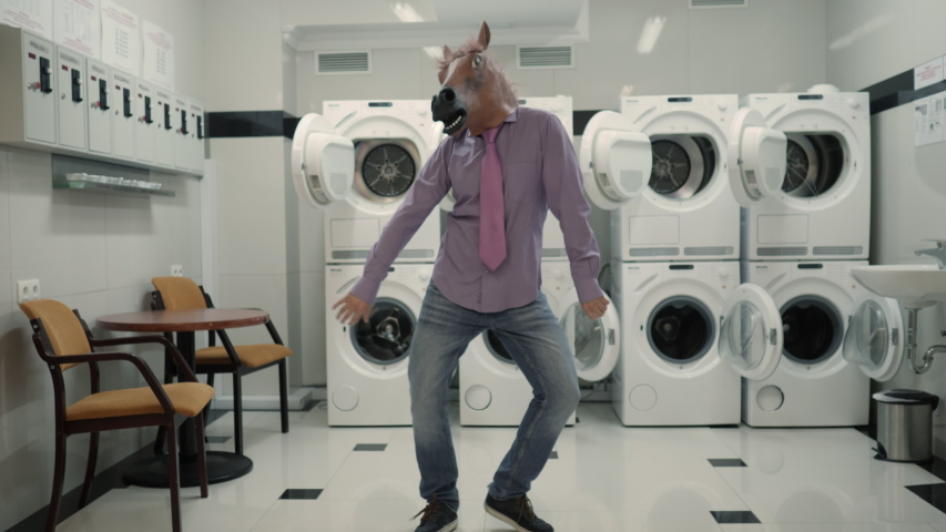 Joyful Man in mask horse Dancing Cheerful In Laundry Room. Man Dancing Viral Dance And Have Fun In Laundry Room. Happy Guy Enjoying Dance, Having Fun Together, Party Halloween. Slow Motion. Halloween | Shutterstock HD Video #1051136251