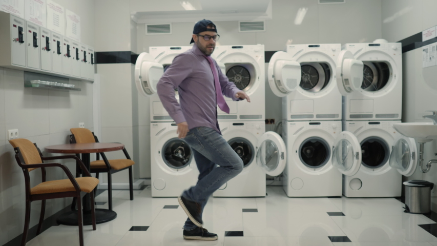 Joyful Man With beard in Cap and Glasses Dancing Cheerful In Laundry Room. Man Dancing Viral Dance And Have Fun In the Laundry Room. Happy Guy Enjoying Dance, Having Fun Together, Party. Slow Motion. | Shutterstock HD Video #1051136266