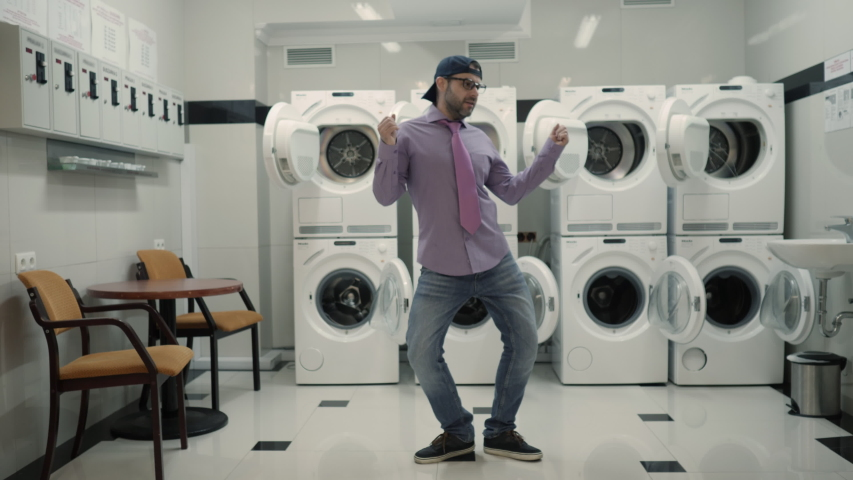 Joyful Man With beard in Cap and Glasses Dancing Cheerful In Laundry Room. Man Dancing Viral Dance And Have Fun In the Laundry Room. Happy Guy Enjoying Dance, Having Fun Together, Party. Slow Motion. | Shutterstock HD Video #1051136275