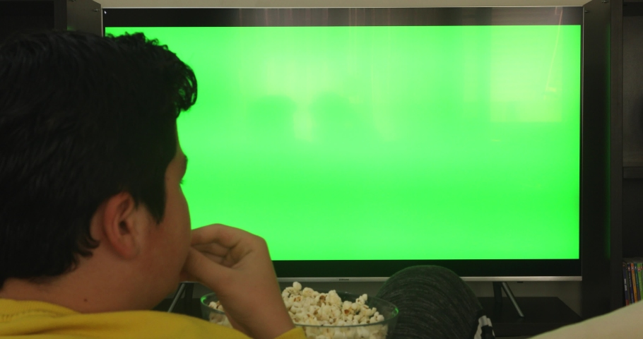 Back view of teenage boy sitting on couch watching green screen television and eating snack at home   Shutterstock HD Video #1051136662