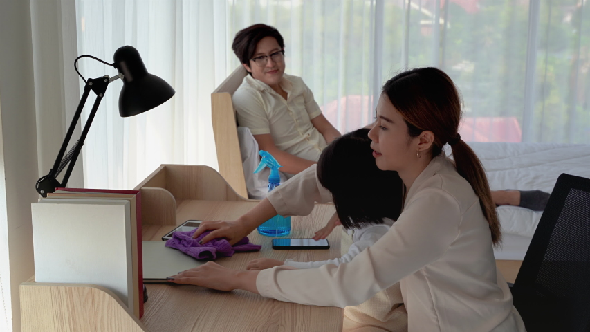 Mother is teaching her daughter to use the spray to clean various devices. Inside the house to be free from germs  | Shutterstock HD Video #1051137967