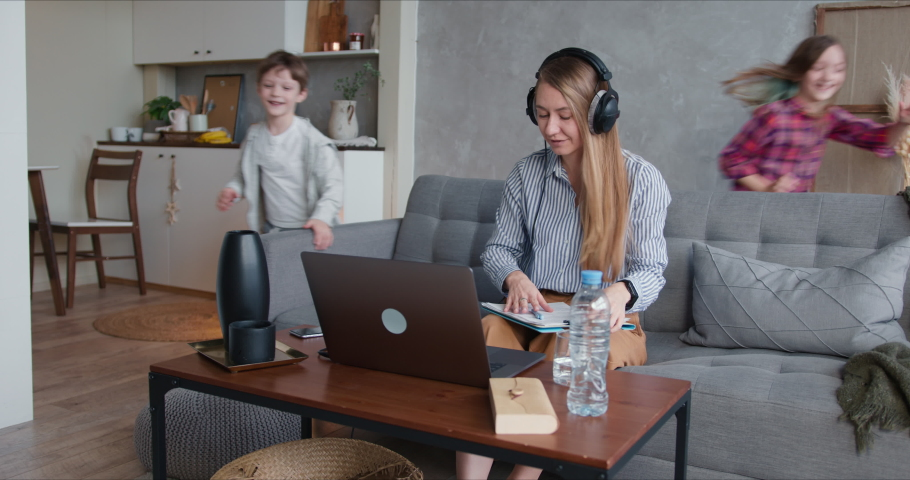 Young happy Caucasian mother is distracted trying to work from home on laptop with two noisy children needing attention. | Shutterstock HD Video #1051144849