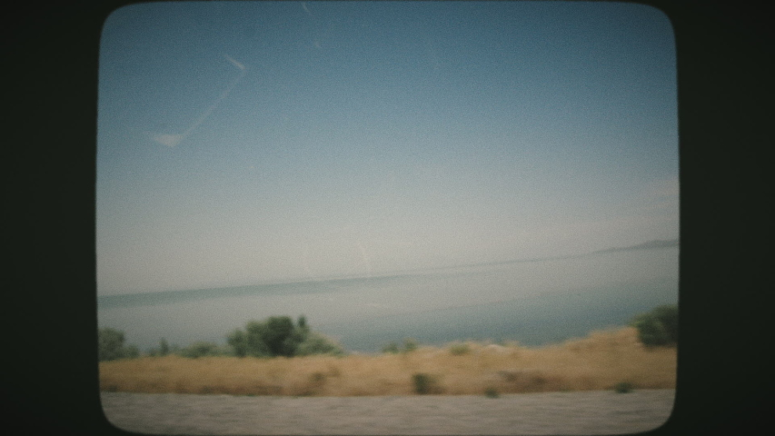 White seagulls flying above the Great Salt Lake on a sunny day, beautiful scenery. View from a car's window. VINTAGE FILM.