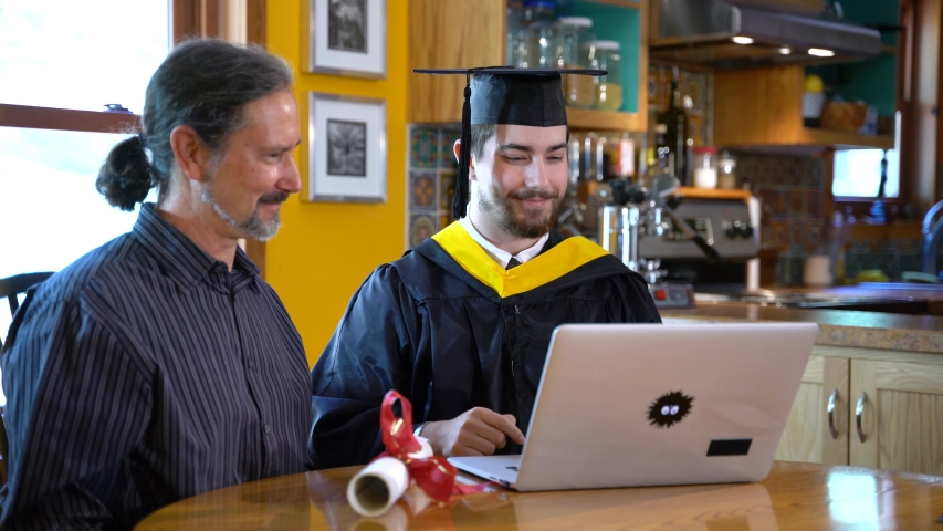 Virtual commencement ceremony for graduation online in a home dining room, and then young man hugs father. Young man looks at camera and gives thumbs up sign.
