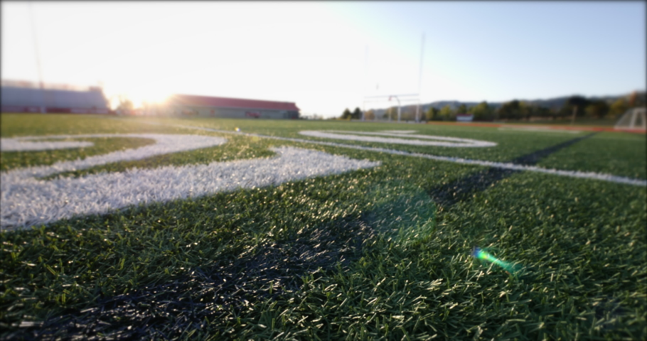 Low-angle slider camera move past the twenty yard line on an empty high school football field with no people.
