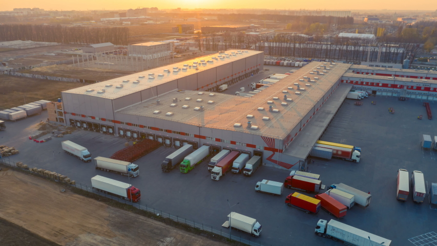 Aerial hyper lapse (hyperlapse - time lapse) of the large logistics park with warehouse, loading hub and semi trucks with cargo trailers standing at the ramps for load/unload goods at sunset Royalty-Free Stock Footage #1051164334