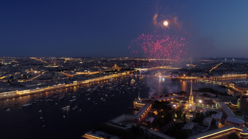 Aerial sideways St. Petersburg festive salute firework over Peter and Paul fortress. Night downtown historical cityscape illumination. Neva river many ships. Road traffic embankment. Day of city Royalty-Free Stock Footage #1051166080