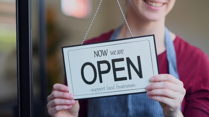Small business owner smiling while turning the sign for the reopening of the place after the quarantine due to covid-19. Close up of woman's hands holding sign now we are open support local business. Royalty-Free Stock Footage #1051196833