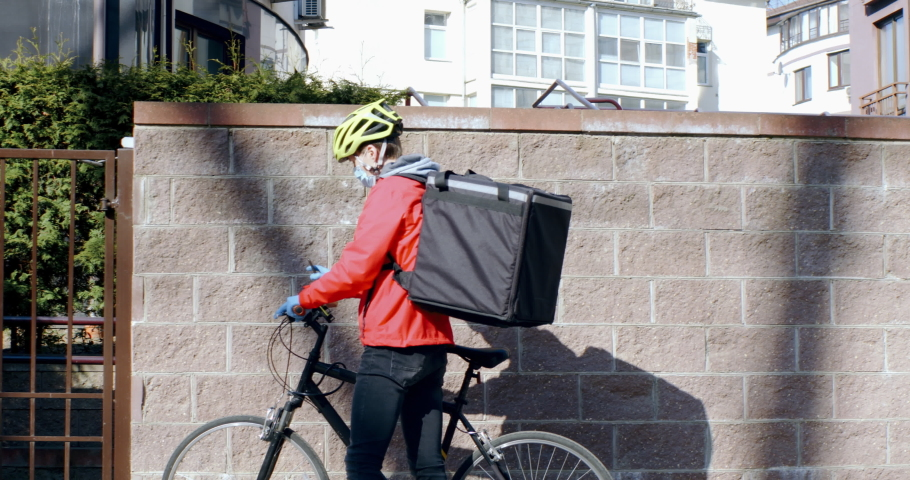 TRACKING delivery man courier wearing medical mask arrives at residential address to deliver food order to customers during virus outbreak. Coronavirus, COVID-19, safe delivery Royalty-Free Stock Footage #1051197190