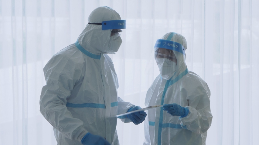 Doctor and nurse in personal protective equipment or ppe treating the patient who had pneumonia from covid-19 or coronavirus infection in isolation room in hospital. medical concept | Shutterstock HD Video #1051201144